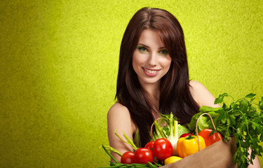 Smiling woman with fruits and vegetables.