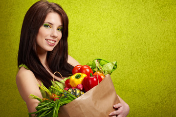 Portrait of a girl holding in hands full of different fruits and