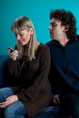 Paar auf einem schwarzen Ledersofa mit einem Handy