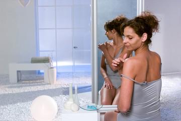 Frau cremt Schulter ein