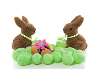 two brown hares with a lot of colorful easter eggs isolated over