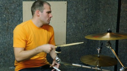 yellow T-shirted drummer playing on drums in recording studio