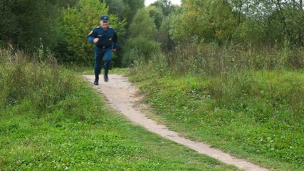 officer of rescue service running on footpath to camera
