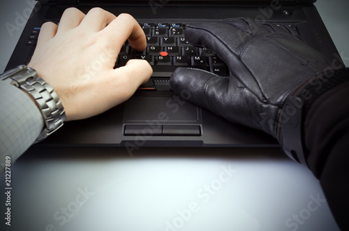 Businessman and hacker hands on laptop keyboard