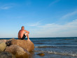 sitting Man on stone seacoast at the sea