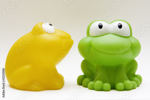 toy rubber blue and yellow frogs on white background