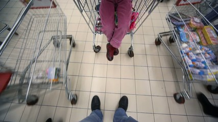 buyers with shopping trolley going in mall, view on floor