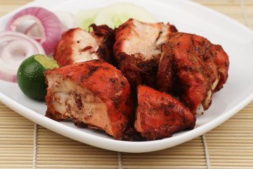 Tandoori Chicken with some garnishing on a bamboo mat