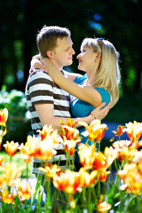 Lover man and girl among red yellow flowers