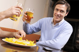 Happy man clinking a mug of beer with his friend