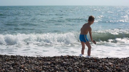 boy standing in sea surf and throwing pebbles to water