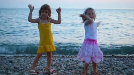 two little girls dancing in evening pebble beach