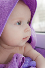 The pure kid in a lilac terry towel looks the surprised sight