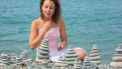 woman building stone stack on pebble beach, sea in background
