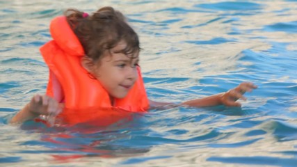 little girl dressed in inflatable waistcoat swimming in pool