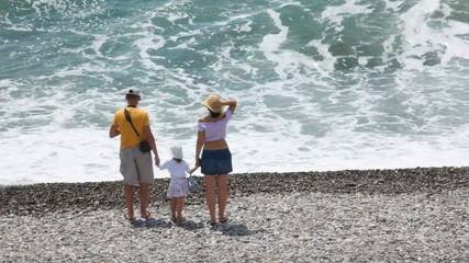 married couple with little daughter looking at waving sea