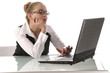 Junge Geschäftsfrau mit Laptop am Schreibtisch