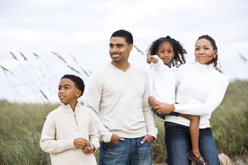 Happy African-American family standing together at beach