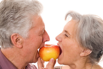 nice elderly couple eating an apple