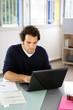 Portrait d'un jeune homme devant ordinateur portable au bureau