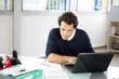 Portrait d'un jeune homme au bureau devant ordinateur portable