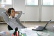 Portrait d'un jeune chef d'entreprise détendu assis à son bureau