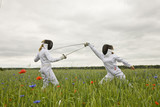 Two girls fencing in a field.