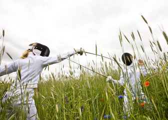 Two girls fencing in a field