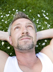 headshot of a bearded man lying in the grass