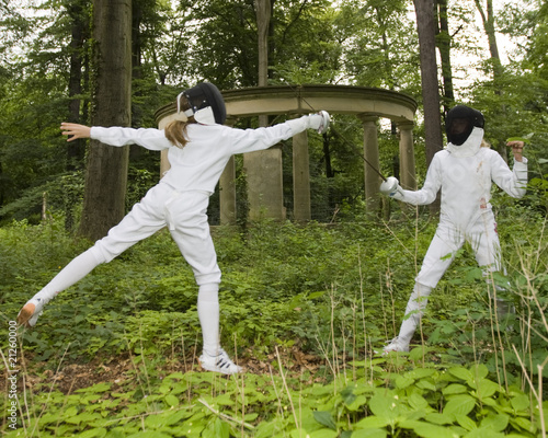 Two girls fencing in the forest.