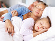 Lovely family sleeping together on bed