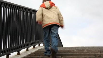 boy runs upwards on steps of stone bridge with an iron handrail