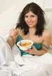 Breakfast in bed, happy female with cornflakes