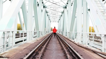 red-haired young man runs forward on camera on railway bridge