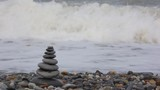 stone stack on pebble beach, waving sea in background