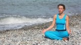 woman in tracksuit sits in pose of lotus on beach against sea