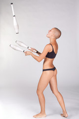 Bald-headed girl juggles