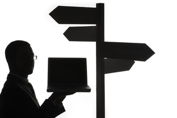 Man with laptop next to directional sign