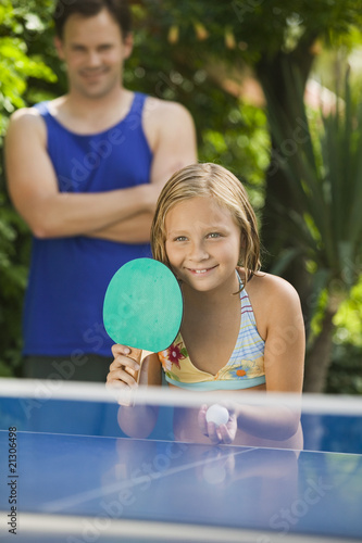 girl (7-9) playing table tennis with father in background.