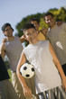 boy (13-15) holding soccer ball with four men at park.