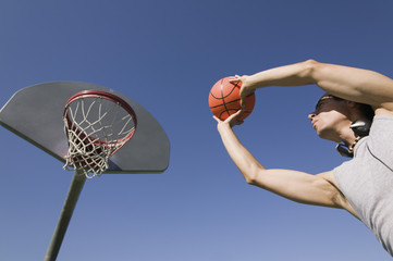 young man playing basketball low angle view.