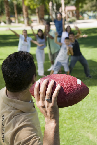 man throwing football to group of people back view.