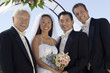 bride and groom with father and best man outdoors (portrait)