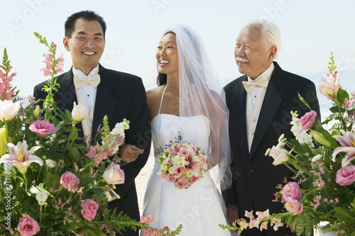 bride and groom with father outdoors