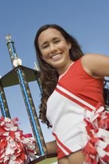 smiling cheerleader holding trophy (portrait) (low angle view)