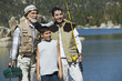 grandfather and two grandsons holding fishing rods standing by lake