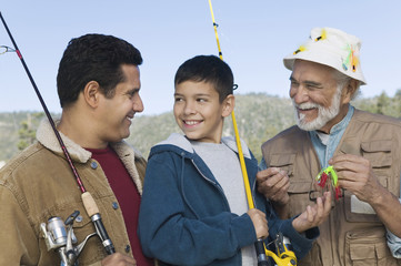 male members of three generation family on fishing trip smiling