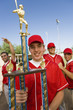 baseball player holding trophy on field team-mates in background