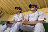 two baseball team-mates sitting in dugout (low angle view)