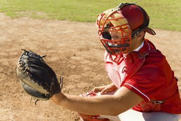 baseball catcher crouching on baseball field